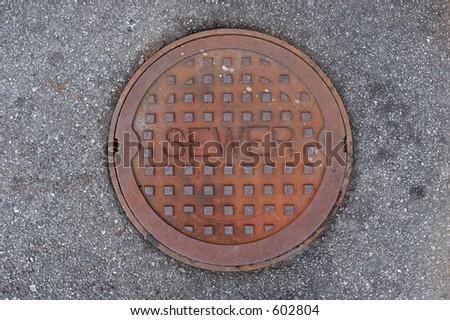 Rusty manhole cover - stock photo
