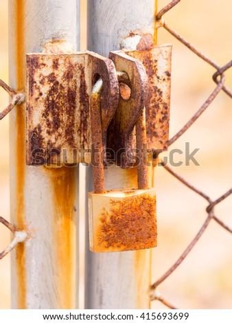 Rusty master key locked on the rusty door with rusty metal net - stock photo