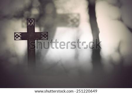 rusty metal cross in spooky dark landscape - stock photo