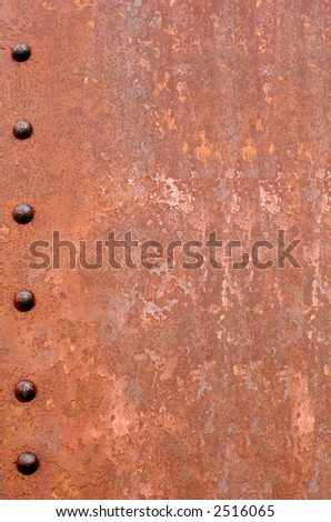 Rusty metal for background.  Six rusted rivets down the left hand side. - stock photo