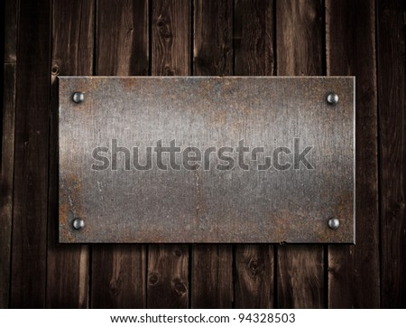 rusty metal plate on wooden background - stock photo