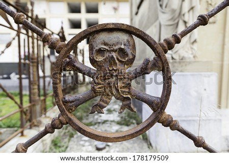 Rusty metal skull in a cemetery, detail of an ancient ornament on a grave - stock photo