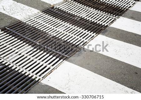 Rusty metal ventilation grille painted in zebra crosswalk on asphalt way. - stock photo