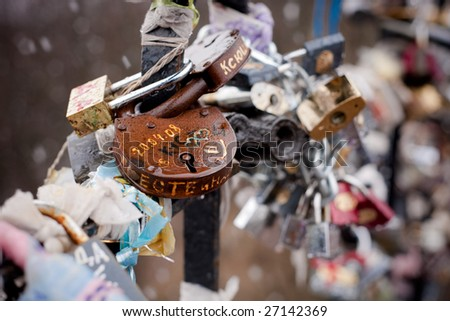 Rusty metall lock with hearts among lots of other locks - stock photo
