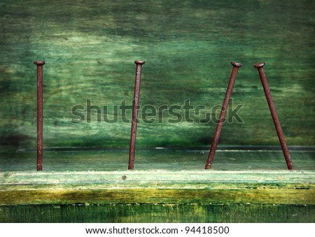 rusty nails in green wood - stock photo