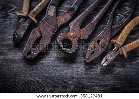 Rusty nippers pliers tin snips wire-cutter on wooden board. - stock photo