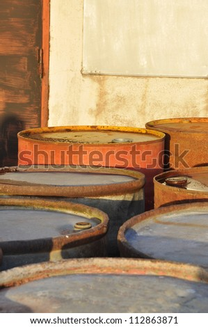 Rusty oil drums in different colors. - stock photo