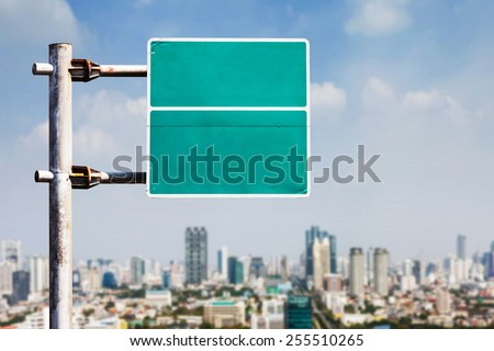 Rusty old and dirty blank road sign with blurry city background - stock photo