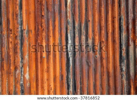 Rusty old corrugated iron fence close up. - stock photo