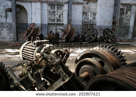rusty old metal gadgets in an abandoned ship factory - stock photo