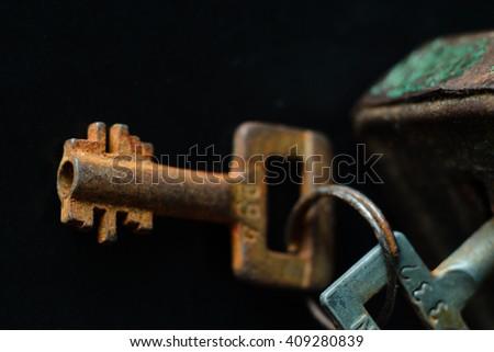 Rusty old metal key on dark background - stock photo