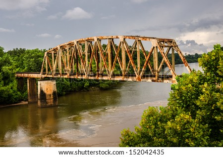 Rusty old railroad bridge spans the Chattahoochee River on the Georgia/Alabama border - stock photo