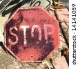 Rusty old stop sign on ground. - stock photo