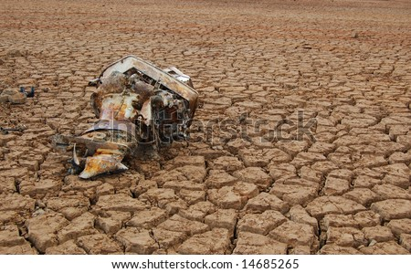 Rusty outboard motor in dry lake - stock photo