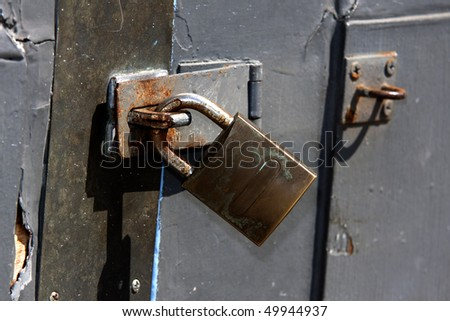 Rusty Padlock on door - stock photo