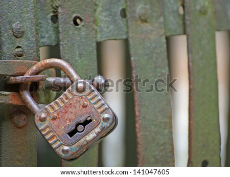 rusty padlock that closes the scratch of an ancient prison of bandits