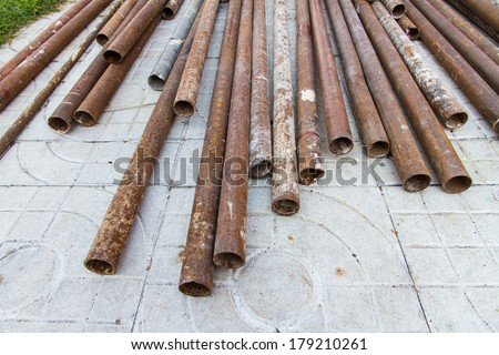 rusty pipe laid in heaps - stock photo