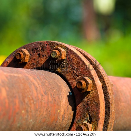 Rusty Pipeline Connection In Front of Green Background - stock photo