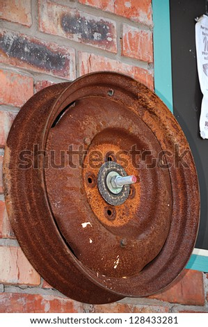 Rusty rim mounted against a wall - stock photo