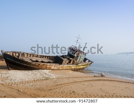 Rusty ship grounded at the beach