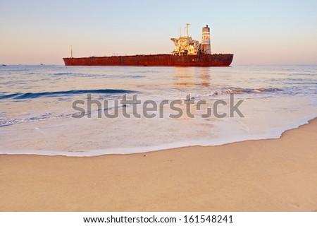Rusty ship on the shoreline in the Goa, India - stock photo