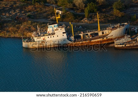 Rusty ships on the sea near the coast. - stock photo