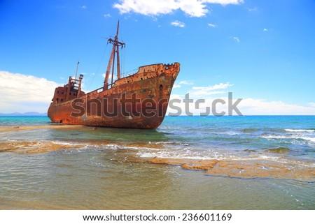 Rusty shipwreck in shallow water on a beach near Gythio, Greece - stock photo