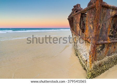 Rusty shipwreck of The Maheno on the yellow sandy beach at Fraser Island, Queensland. Colorful layers in the sky at twilight. Clear water and blue sea. Deserted. Copy space to the left. - stock photo