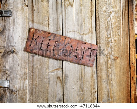 Rusty sign reading 'KEEP OUT'. It is hanging on an old weathered wooden door. Horizontal shot. - stock photo
