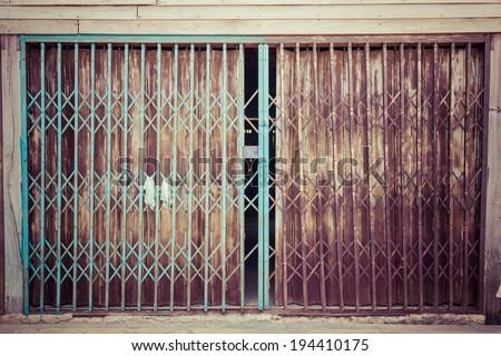 rusty sliding metal door in suburb of Thailand, process color - stock photo