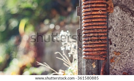 Rusty spring of a parking garage door - stock photo