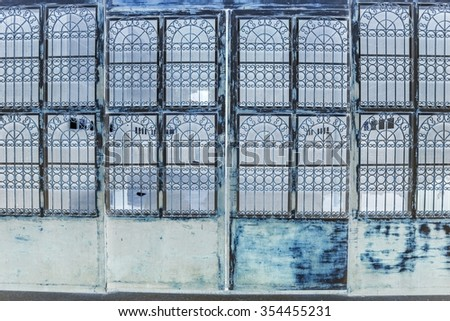 Rusty steel collapsible door texture, old fashion style shutter gate - Old red folding metal door gate  (invert picture style) - stock photo