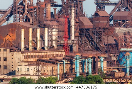 Rusty steel factory with smokestacks at sunset. metallurgical plant. steelworks, iron works. Heavy industry in Europe. Air pollution from smokestacks, ecology problems. Industrial landscape - stock photo