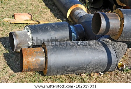 Rusty steel pipe with heat insulation on construction site - stock photo