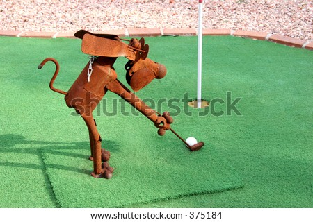 Rusty tin dog playing golf. - stock photo