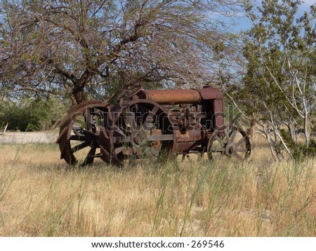 Rusty tractor in desert with metal wheels, side view.