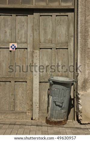 rusty trash can in front of old wooden door - stock photo