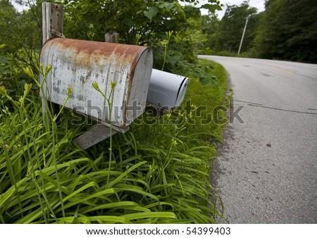 Rusty U.S. mail box in a rural community - stock photo