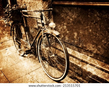 Rusty vintage bicycle leaning with on wooden board (useful for entering a text advertisement, menu etc) and carrying plants in wooden box as decoration.  Retro aged photo with scratches. - stock photo
