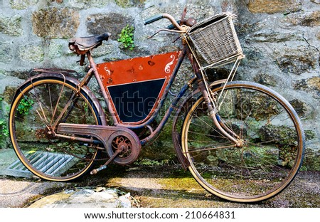 Rusty vintage bicycle with black board for entering a text (advertisement, menu etc) and wicker basket leaning on a stone wall. Brittany, France.  - stock photo