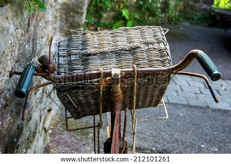 Rusty vintage bicycle with wicker basket leaning on a stone wall. Brittany, France. Closeup. Back view. - stock photo