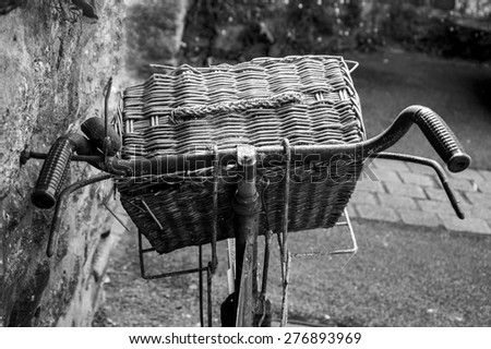 Rusty vintage bicycle with wicker basket leaning on a stone wall. Closeup. Back view. Aged photo. Black and white. - stock photo