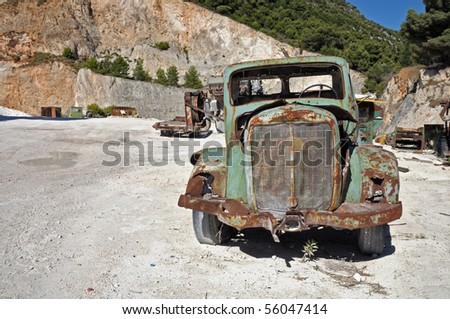 Rusty vintage car and industrial machinery at a quarry. - stock photo