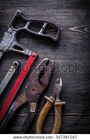 Rusty vintage handsaw wire-cutter pliers on wooden board construction concept. - stock photo