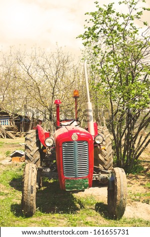Rusty vintage tractor in countryside - stock photo