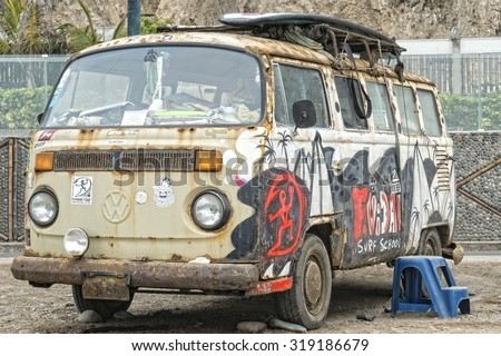 Rusty Volkswagen van wreck  in Lima Peru, used as a surfboard equipment storage. - stock photo