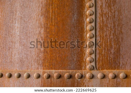 Rusty wall with rivets - stock photo