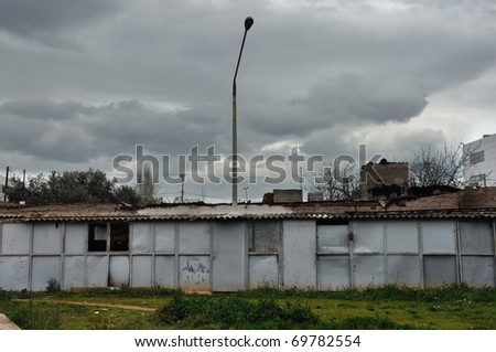 Rusty warehouse shack under moody sky. Street light emerging through the roof drying laundry by the window.