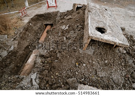 Rusty water pipe in a trench ground from above view. Repairing of the water delivery system. Open trench with water pipe and heap of ground near. Industrial plumbing concept.