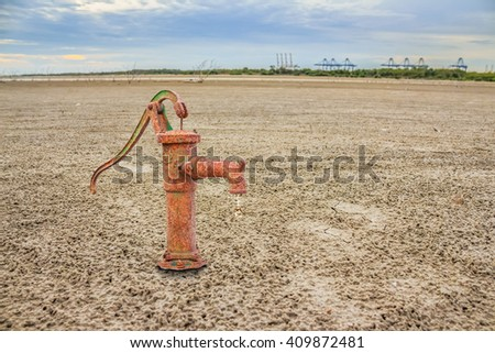 Rusty water pump on land with dry and cracked ground. Desert - stock photo